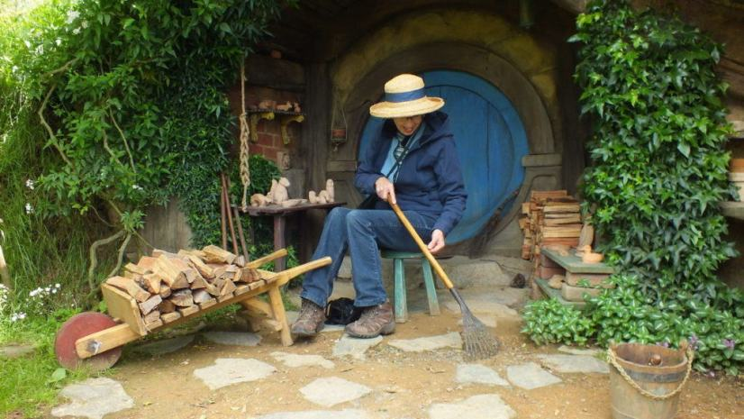 An image of a Jean using a hobbit leaf rake at Hobbiton in New Zealand. Photography by Frame To Frame - Bob and Jean.