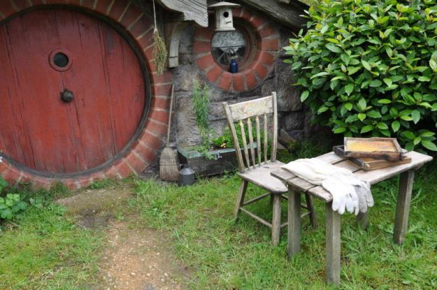 An image of a small table with bee keeper gloves and two honeycombs on it at the home of the beekeeper in Hobbiton in New Zealand. Photography by Frame To Frame - Bob and Jean.