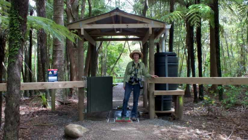 An image of Jean at the entrance gate to the Waitakere Ranges hiking trails, New Zealand.