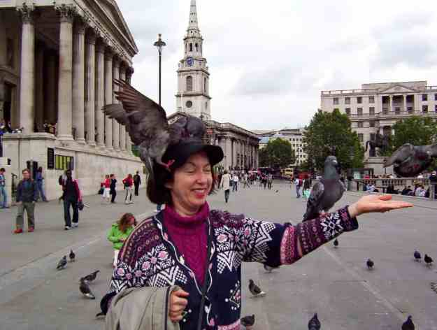 An image of pigeons sitting on a person in Trafalgar Square in London, England.