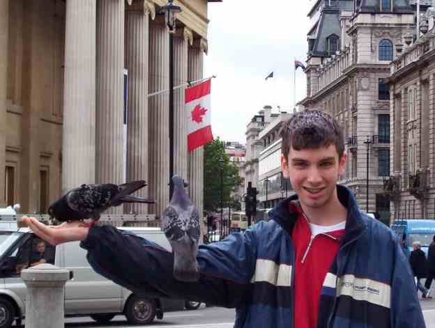An image of pigeons feeding out of hand in Trafalgar Square in London, England.