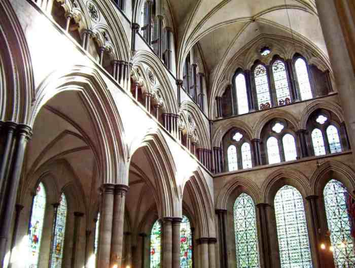 the interior of Salisbury Cathedral showing pointed arches, columns, windows and doors.