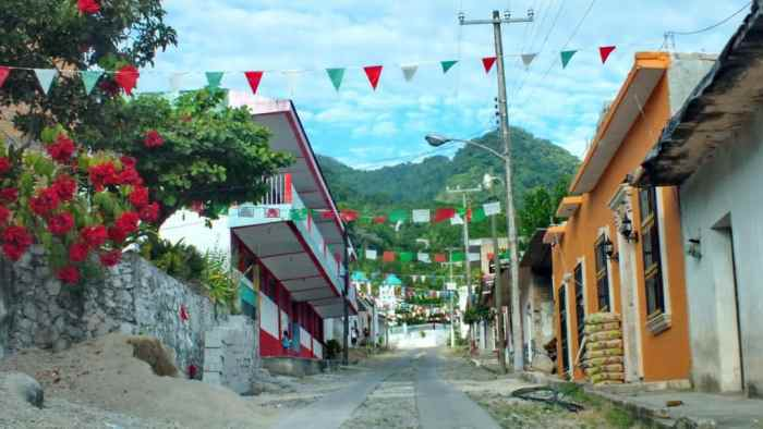 Image of red, white and green banners gaily strewn overhead in the town of La Bajada, Mexico.