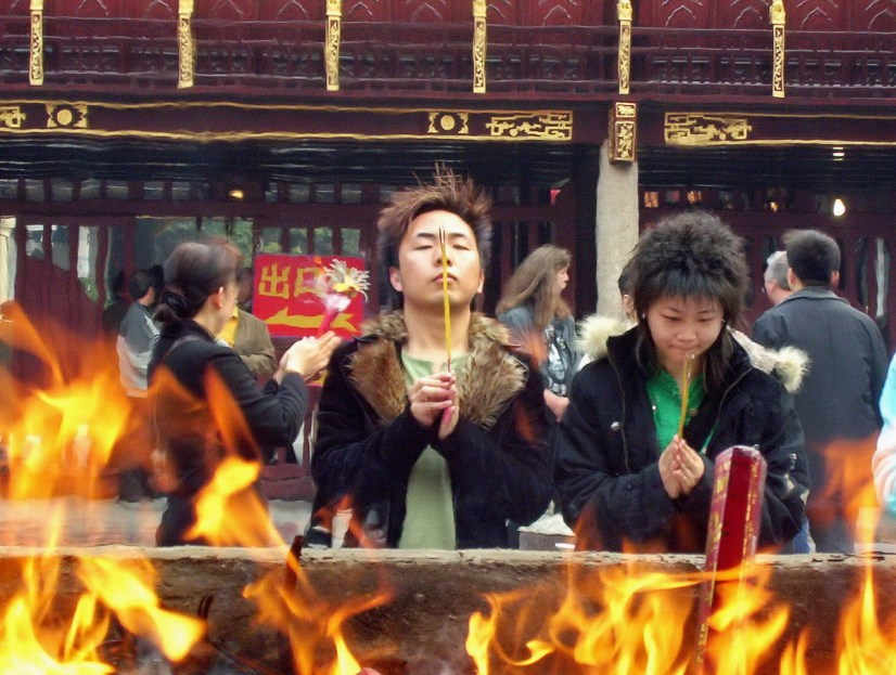 A young couple pray will holding their burning incense sticks inside the City God Temple of Shanghai, in Shanghai, China.