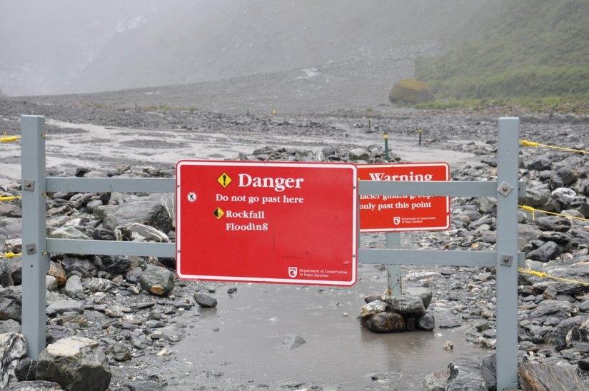 warning signs at fox glacier, south island, new zealand