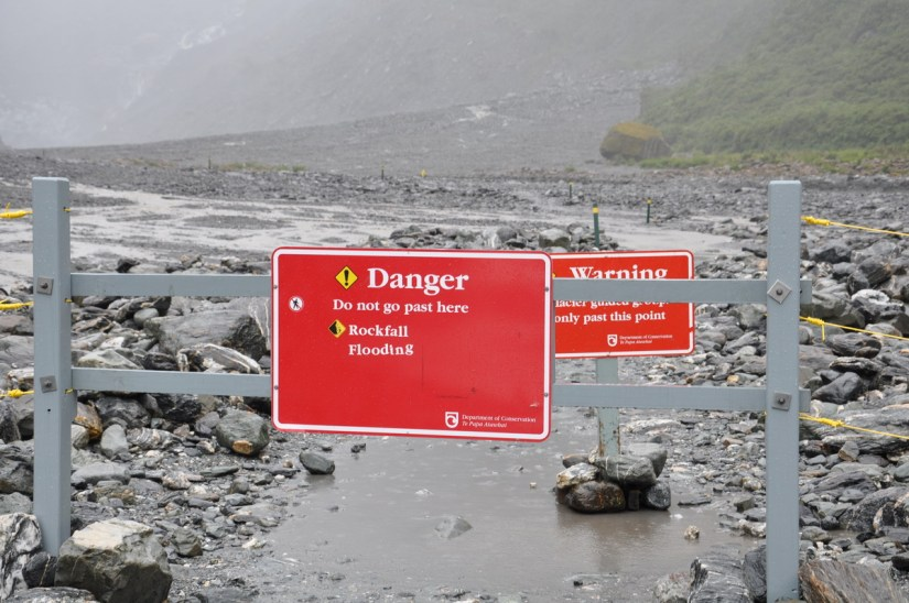 warning signs at fox glacier, south island, new zealand