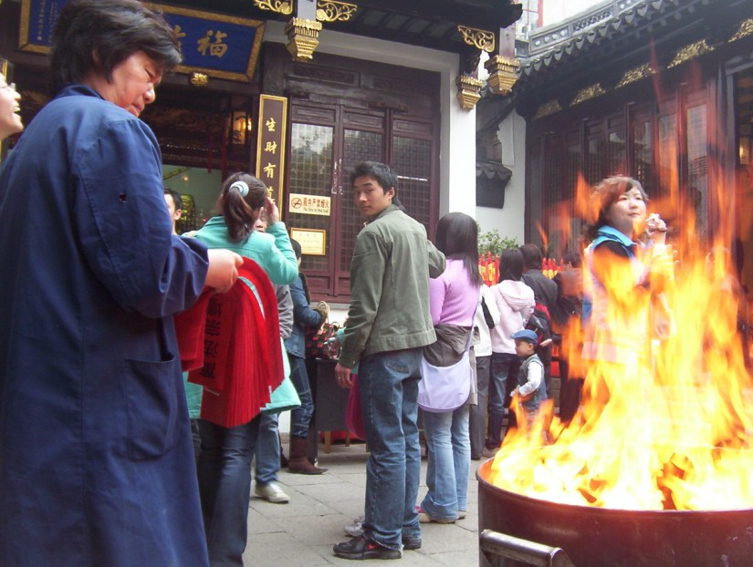 People lineup to receive their red joss paper outside the City God Temple of Shanghai in China.