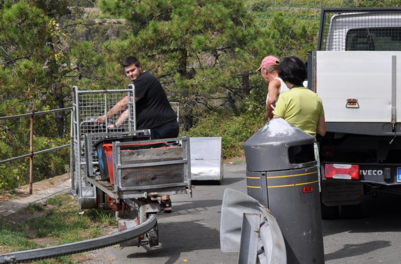 workers unloading a monorail, cogwheel railway, cinque terre, italy