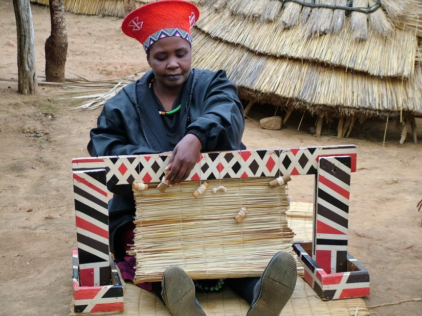 a married zulu woman weaving a grass mat, shakaland, kwazulu-natal, south africa