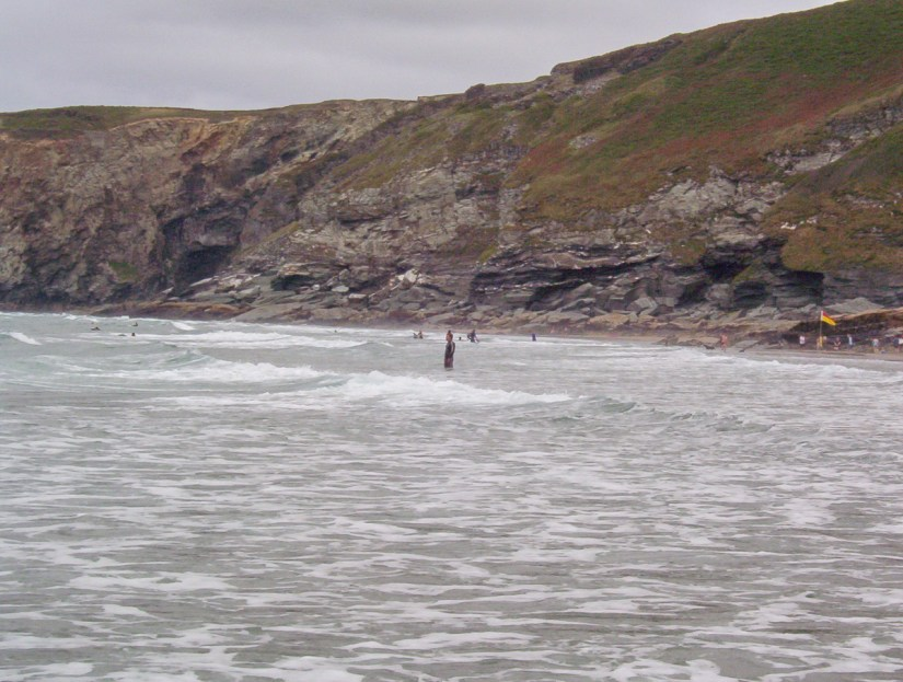 swimmers at trebarwith strand beach, cornwall, england
