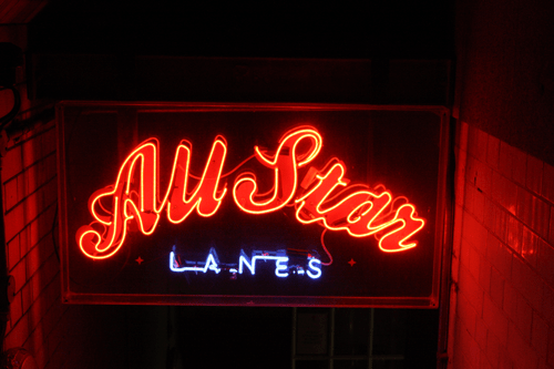 all star lanes london bowling alley and diner review; the all star lanes logo sign in neon above the stairs to enter