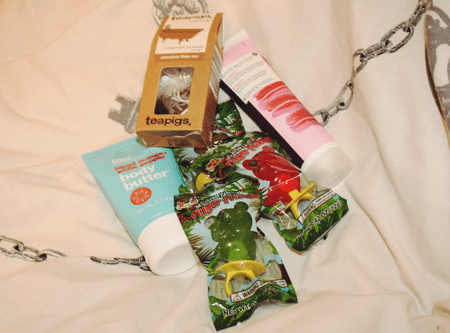 teapigs tea in a carton, korres hand lotion in its tube, bliss body butter in its tube, and a selection of teddy bear rings in their packaging, all on a bedspread