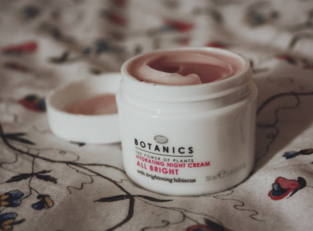 Botanics All Bright Hydrating Night Cream with the lid open sitting on an IKEA duvet
