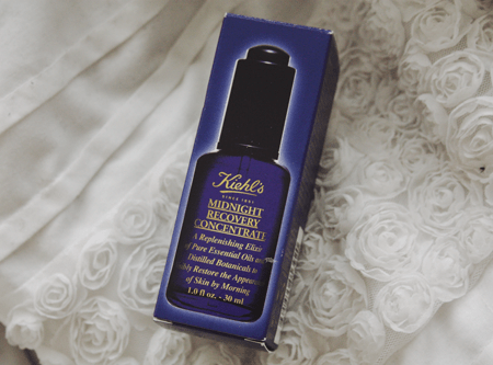 Kiehl's Midnight Recovery Concentrate sitting in its original packaging, on an embroidered white floral duvet