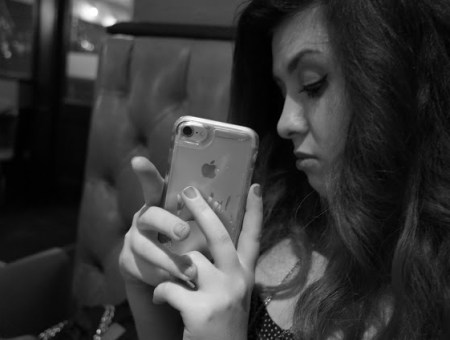 a black and white picture of a girl (francesca sophia) holding her phone up and taking a picture of the photographer; she is not smiling, and has winged eyeliner, and long, dark, curled hair.
