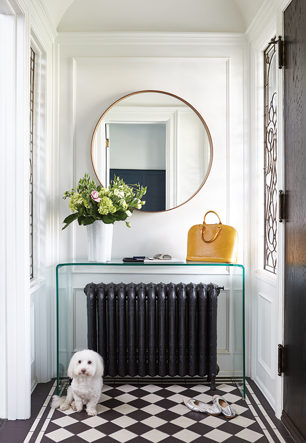 foyer, entry, black radiator, lucite console table, white walls, checkerboard floor
