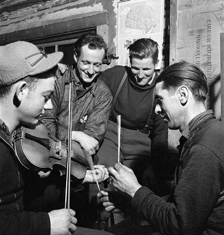 Black and white photo of four men , one playing the fiddle and another using sticks for percussion while the other two listen and watch.