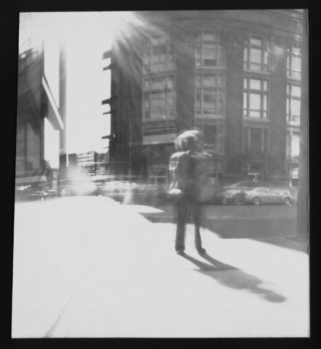 Yesterday, I was out testing exposure times for the pinhole cameras I made for my upcoming workshop for Nuit Blanche Winnipeg. Here is my favorite shot of the day. It is of a woman who was waiting for a bus and kept staring at me. She was probably wondering what I was doing with all of these cookie tins covered in cardboard and tape. Luckily she stood in one spot for long enough that I was able to capture her figure in the image.