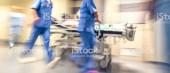 Doctors and nurses pulling hospital trolley,