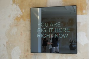 "Foto: Texttafel ""Your are right here right now"" auf unverputzter Wand"