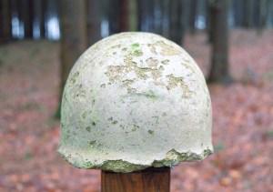 Foto: Maroder Betonabguss eines Stahlhelms im Wald