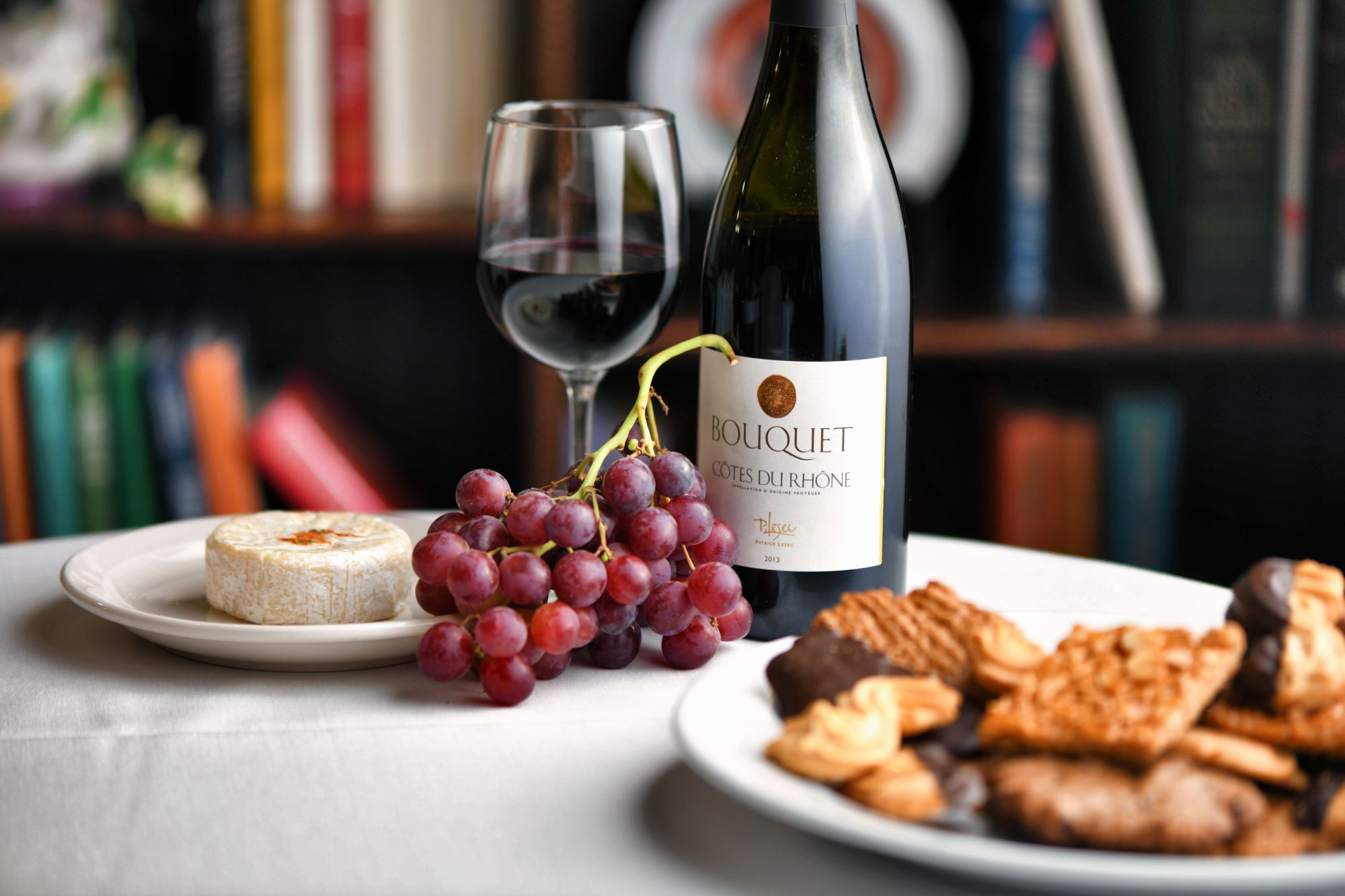 Red grapes, brie cheese, Cotes Du Rhone, plate of chocolate and butter cookies