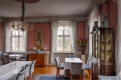 Rosa Salon im Kleinen Schloss. Das Bild bietet zugleich einen Blick in den Schlosspark mit dem Fluss Bober
