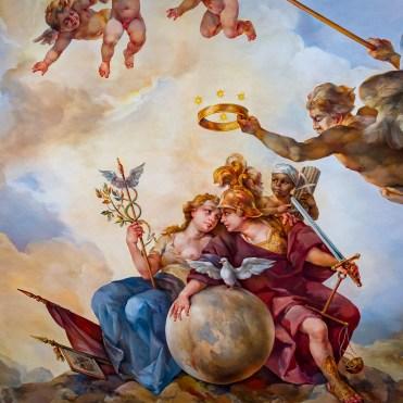 Justitia und Mars thronen im Zentrum des Deckengemäldes an der Erdkugel. Die Taube in der Mitte kann als Symbol der Versöhnung gesehen werden