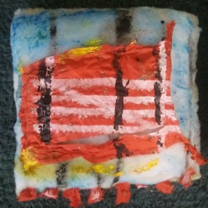 Image shows: square white cushion with 8 small red prayer flags sewn to bottom edge. A white gate symbol is stenciled onto a fragment of red silk fabric song with three vertical black lines and hints of blue and yellow paint.