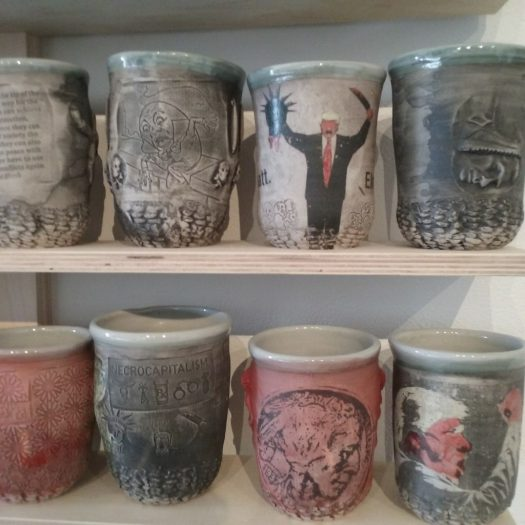 A detail of 8 cups on simple wooden shelves. One features an image of Trump holding a severed head of the Statue of Liberty, another a screaming Trump face. The other cups are subdued and have images of war impressed into them