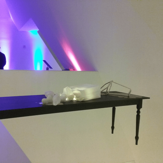 One side of The Enchanted, a sculpture featuring a long end of a low wooden table protrudes from a wall in mid air, with several white rubbery looking shapes placed on it, some are lit from within.
