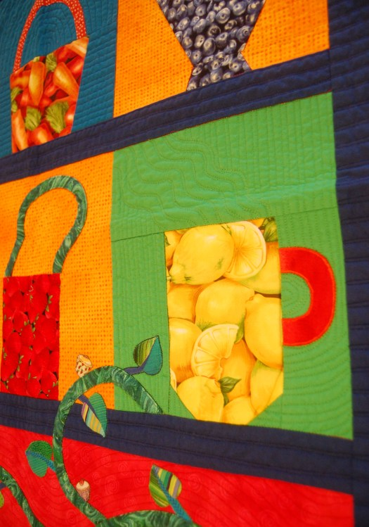 Bright blocks of color with object shapes such as a cup made out of a print of lemons and a basket made our of a print of strawberries.