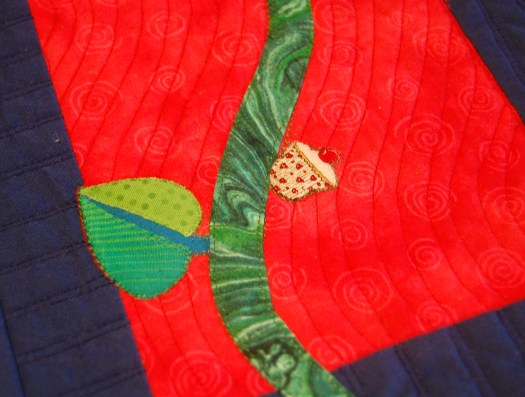 Detail of whimsical quilt featuring a cut-out of a cupcake added to green stem as if it were a fruit, with mottled green leaf to balance and a wavy quilting pattern over the whole design