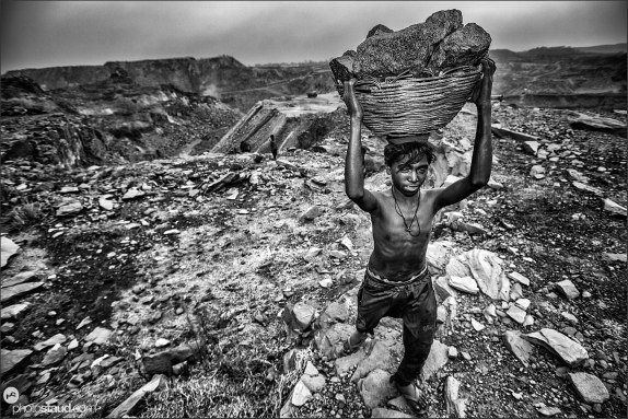 Boy carrying basket full of coal that he has collected from a government mine in Dhanbad, India
