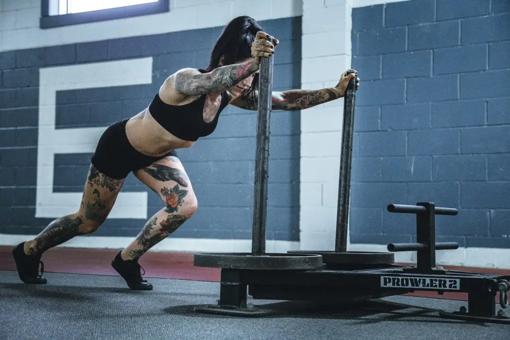 Woman do strength training program for women with home gym equipment
