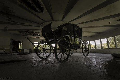 A low angle shot of an old carriage Inside a very unique abandoned house with a gothic style.