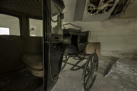 An old carriage Inside a very unique abandoned house.