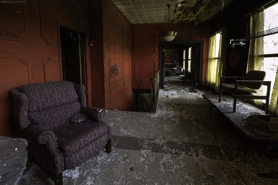 Inside the foyer of a very unique abandoned house with a gothic style.