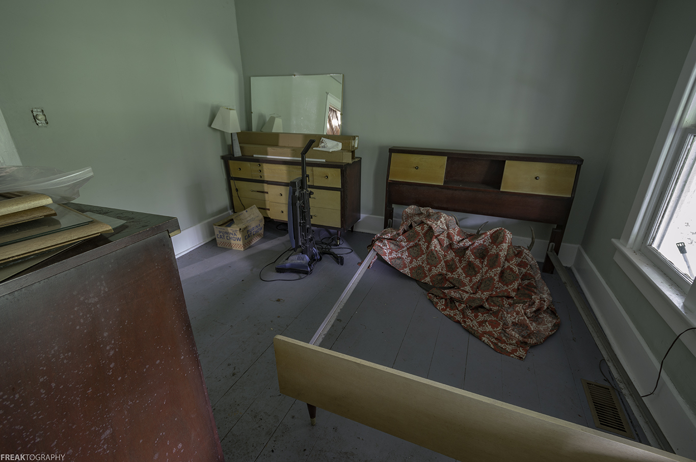 A sheet covers two strange items n the bedroom of an abandoned house