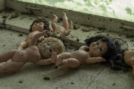 Dolls, found scattered over the kitchen cupboard inside an abandoned house