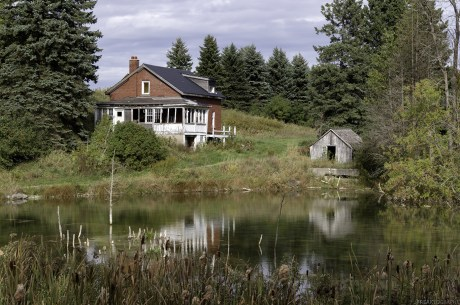 An abandoned Ontario house reflects in a pond.