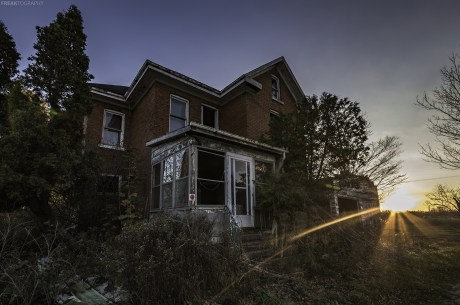 A photo of the sunsetting behind an abandoned Ontario House