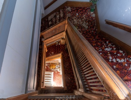 abandoned 1980s hotel staircase view.