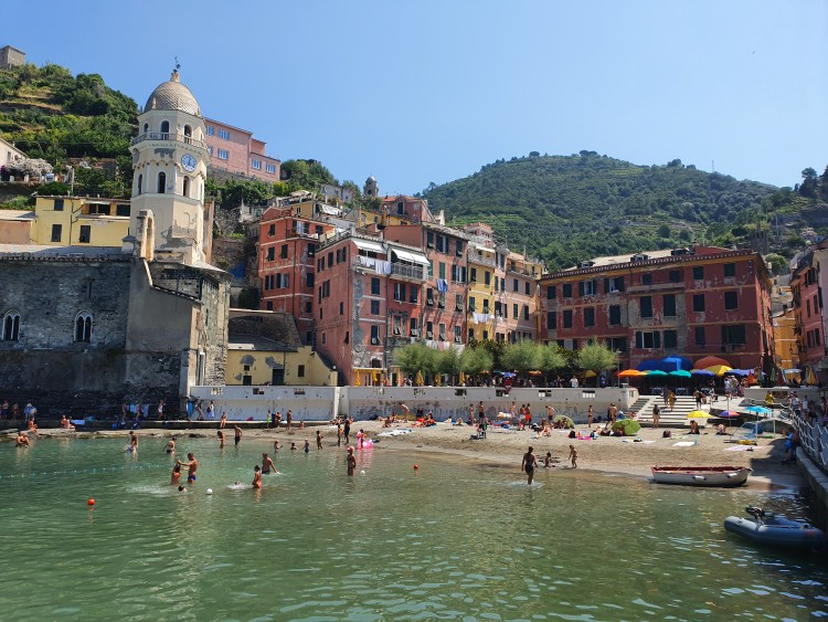 The village of Vernazza in Cinque Terre, Italy.  People play in the water and along the shore surrounded by colorful architecture from the Middle Ages.