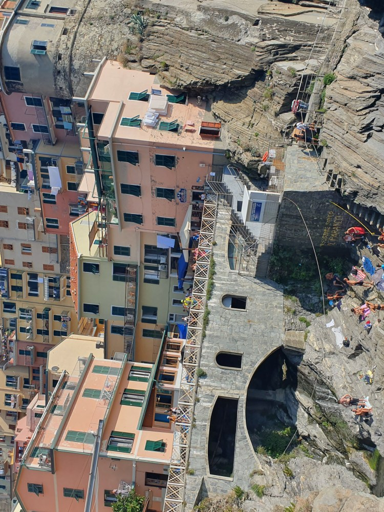 The village of Manarola in Cinque Terre, Italy on a sunny day.  The colorful architecture climbs the side of the mountain and people splash in the swimming lagoon and jump from rocks.