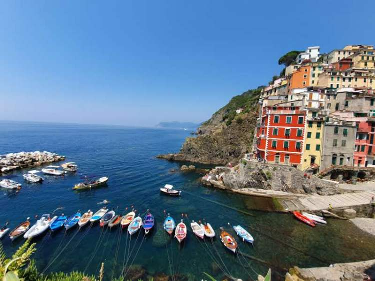 Colorful boats are tied to the shore of Riomaggiore in Cinque Terre, Italy.