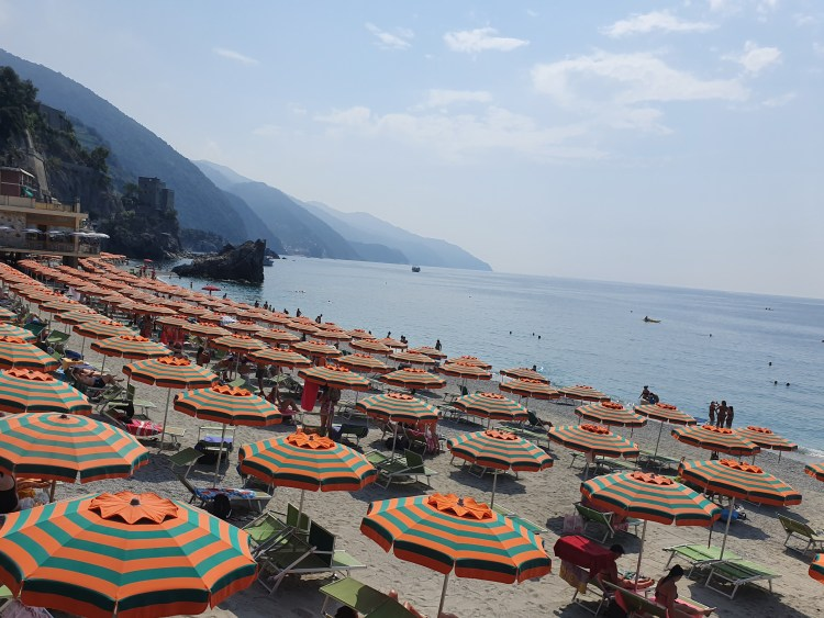 Beach of Monterosso in Cinque Terre, Italy. Orange and green striped umbrellas line the shore of the Mediterranean Sea.