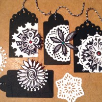 Paper lace doilies on elegant black and white gift tags with flowers
