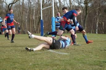 2) En fremadstormende Hans Erik Severinsen, iført Erritsøs blå-røde trøje, har væltet en modstander og tackles i høj fart af en anden forsvarende Hundestedspiller, som dog ikke kan forhindre scoring. Foto: Natasja Brodersen / Erritsø GIF Rugby.