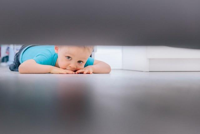 enfant regardant sous le lit durant une seance photo a domicile paris frederico santos photographe